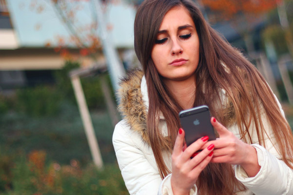 Worried teen looking at phone